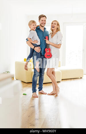 Portrait of happy family in living room of their new home - Stock Photo