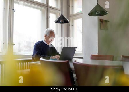 Senior man using laptop on table at home