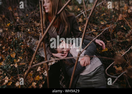 Portrait of little girl with head in her mother's lap in autumnul nature