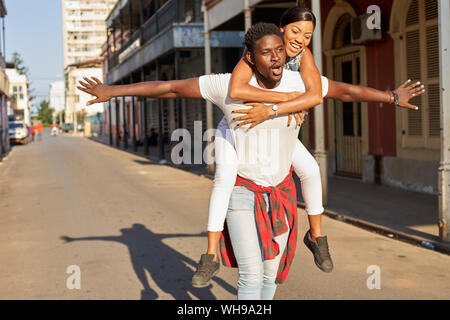 Young man carrying girlfriend piggyback in the street, Mabuto, Mozambique