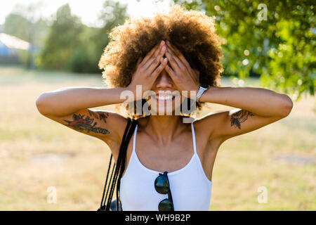 Smiling tattooed young woman in summer covering eyes with her hands
