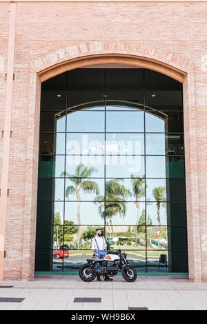 Man standing with motorbike standing in front of glass facade - Stock Photo