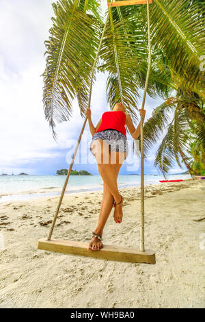 Woman swinging on tropical beach of Anse Volbert with Islet of Chauve Souris in the background, Cote d'Or, Praslin, Seychelles - Stock Photo