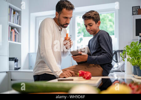 Father and son using tablet and cooking in kitchen at home together