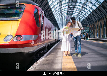 Young couple standing on platform looking at map, London, UK - Stock Photo
