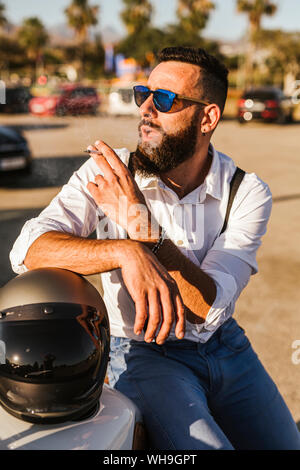 Portrait of bearded motorcyclist with mirrored sunglasses leaning on his helmet smoking - Stock Photo