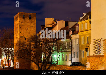 Ccity wall tower and traditional houses at night, Warsaw, Poland - Stock Photo