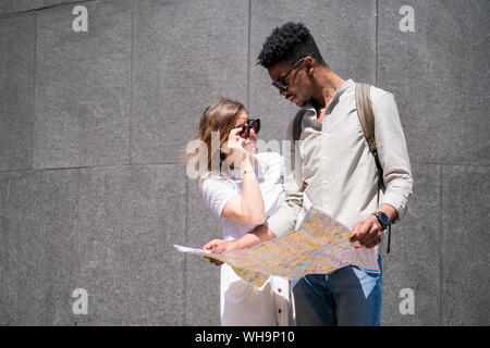 Young couple with city map, London, UK - Stock Photo