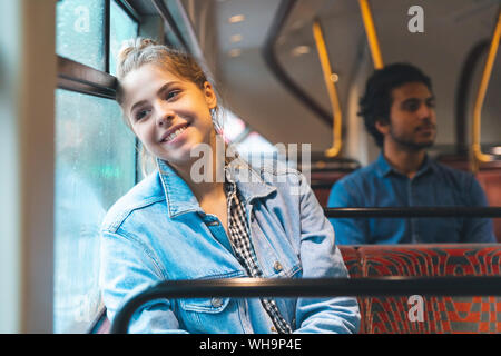 Portrait of happy young woman travelling by bus, London, UK