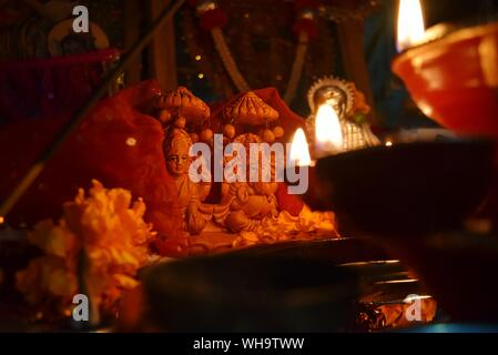 Lit Oil Lamps In Front Of God And Goddess Statues