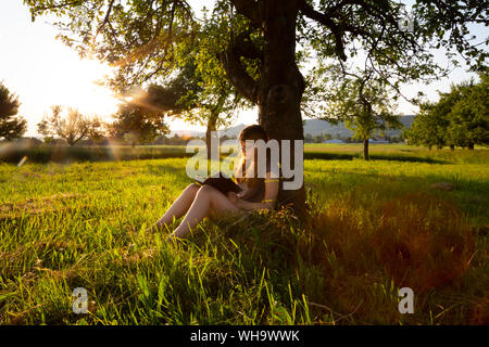 Little girl leaning against tree trunk at sunset reading a book