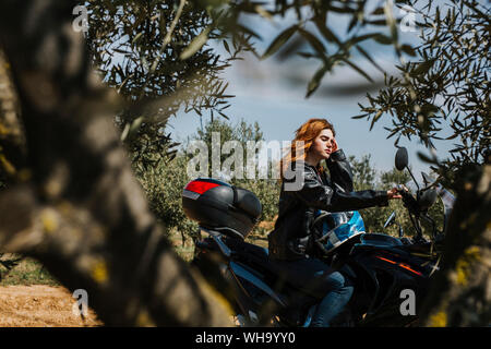 Redheaded woman on motorbike, Andalusia, Spain - Stock Photo