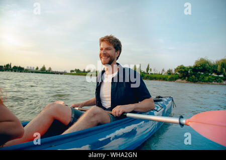 Confident young caucasian man kayaking on river with sunset in the backgrounds. Having fun in leisure activity. Happy male model laughting on the kayak. Sport, relations concept. - Stock Photo