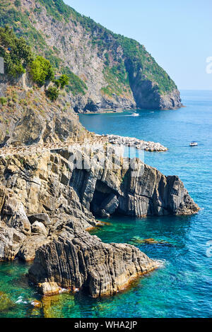 Rocky coast near Riomaggiore with part of the Love Road (Via dell'Amore) in Cinque Terre National Park, Italy - Stock Photo
