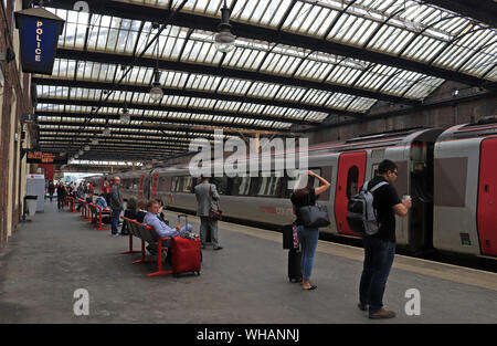 A Cross Country train arrives at Stoke on Trent railway station forming a service to Bristol Temple Meads as passengers wait to board. - Stock Photo