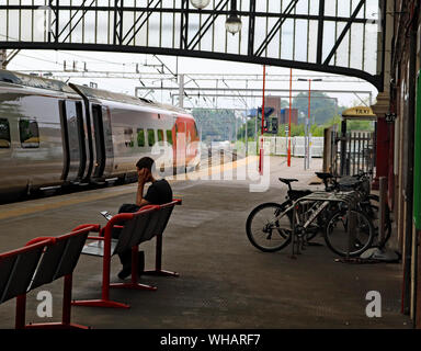 A Virgin train stands at Stoke on Trent railway station forming a service to London Euston as a passenger waiting for another train makes a phone call - Stock Photo