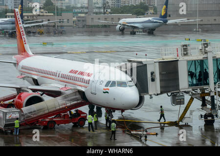 INDIA, Mumbai , Chatrapati Shivaji International Airport, Airbus of Air India, ground staff service team and boarding passenger on boarding bridge, behind Mumbai skyline and aircraft of private airline Jet Airways which went in insolvency in 2019 - Stock Photo