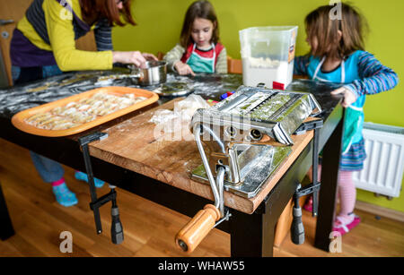 High Angle View Of Mother With Daughters Preparing Food In Kitchen - Stock Photo