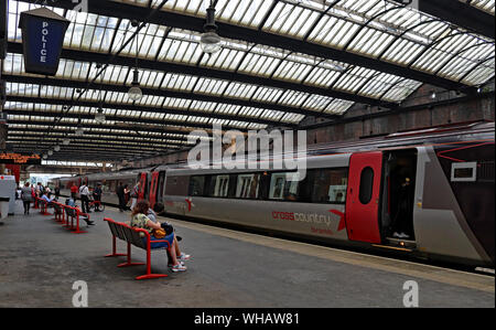 A Cross Country train stands at Stoke on Trent railway station forming a service to Bournemouth as passengers board or wait for their train. - Stock Photo