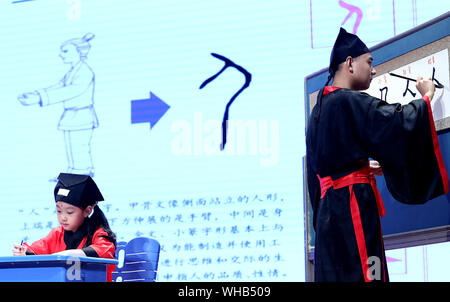 Shanghai, China. 2nd Sep, 2019. A teacher (R) demonstrates how to write Chinese character 'ren', which means person or human, during an event marking the symbolic first class of the new semester at a primary school in Shanghai, east China, Sept. 2, 2019. Credit: Chen Fei/Xinhua/Alamy Live News - Stock Photo