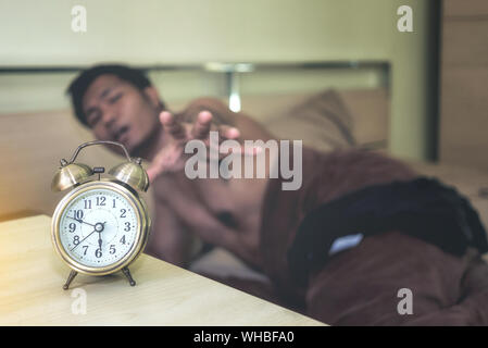 Young Man Reaching Alarm Clock While Lying On Bed At Home - Stock Photo