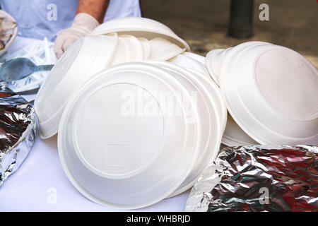 A pile of plastic plates on the street. Ban disposable plastic utensils. Ecology concept. Close-up - Stock Photo