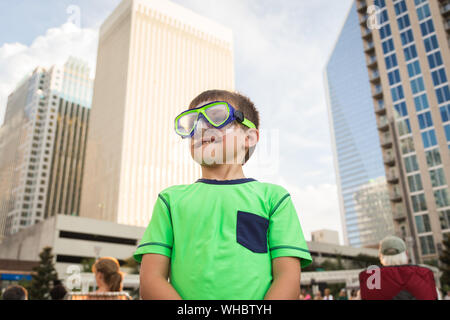 Boy Wearing Swimming Goggles While Standing Against Buildings - Stock Photo