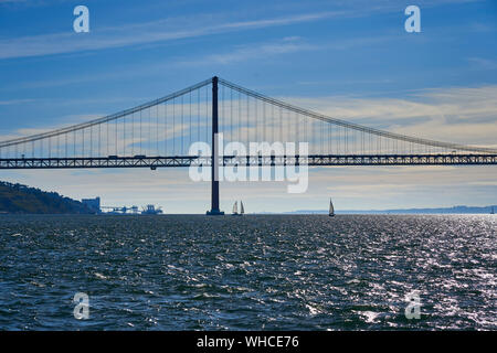 Sailing on Tagus river with Ponte 25 de Abril in background Lisbon, Portugal. - Stock Photo