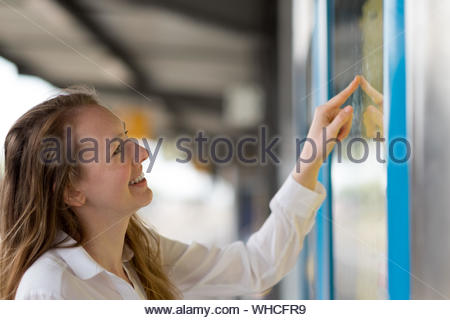 Young woman reading a train timetable on an open-air platform as she checks the schedule with a smile, close up profile view - Stock Photo