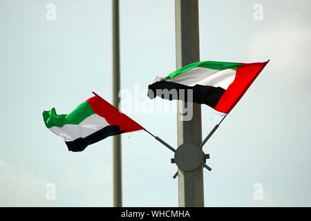 Low Angle View Of United Arab Emirates Flag On Pole Against Sky - Stock Photo