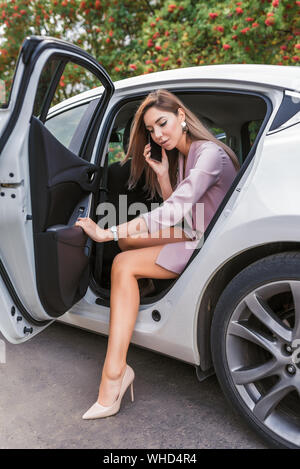 Business lady talking on phone, summer city taxi, getting out car, door opens, serious meeting an important call, business sedan in city taxi. Long ha - Stock Photo
