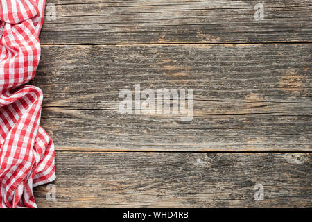 Red checkered picnic textile on rustic wooden planks background. Top view copy space. Cooking, food menu background - Stock Photo