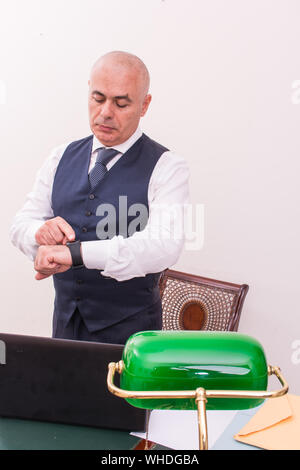 Businessman Looking At Wristwatch While Standing At Desk In Office - Stock Photo