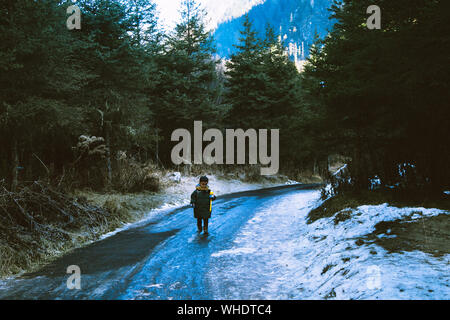 Boy Walking On Road In Forest During Winter - Stock Photo