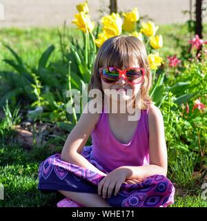 Portrait Of Girl Wearing Sunglasses While Sitting On Field At Park - Stock Photo