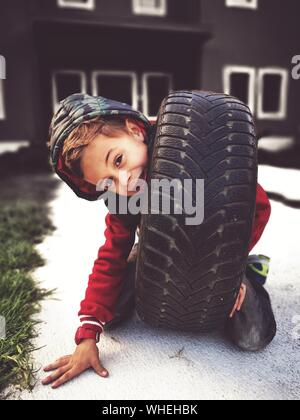 Portrait Of Boy Playing With Tire On Footpath - Stock Photo