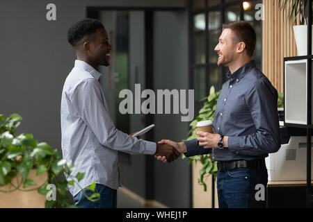 Two happy diverse male colleagues handshaking standing in modern office