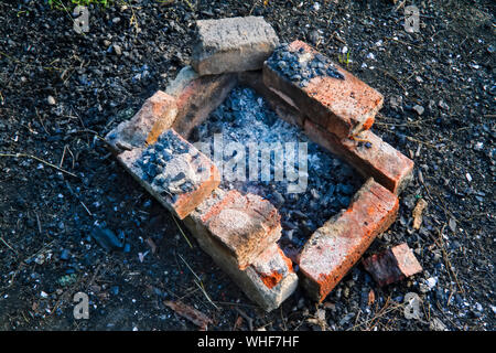 Extinct homemade red brick barbecue in the forest close-up. - Stock Photo