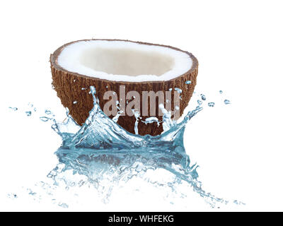 Close-up Of Halved Coconut Splashing On Water Against White Background - Stock Photo