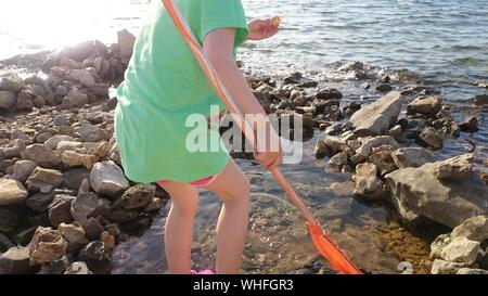 Rear View Of Woman Holding Oar And Standing On Shore - Stock Photo