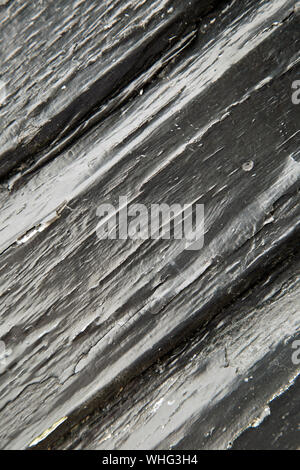 Distessed wooden panel painted black and shot diagonally in portrait format for use as a background - Stock Photo