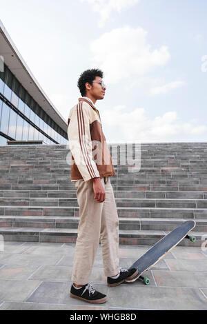 Afro skateboarder stepped on skateboard in street - Stock Photo