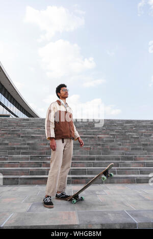 African skateboarder stands and lifts skate in air - Stock Photo