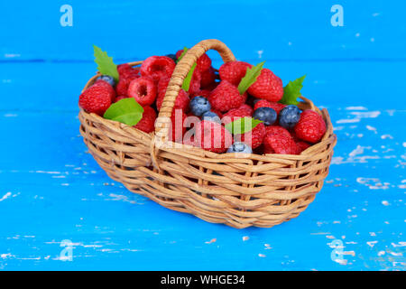 Raspberries And Blueberries In Basket On Wooden Table - Stock Photo