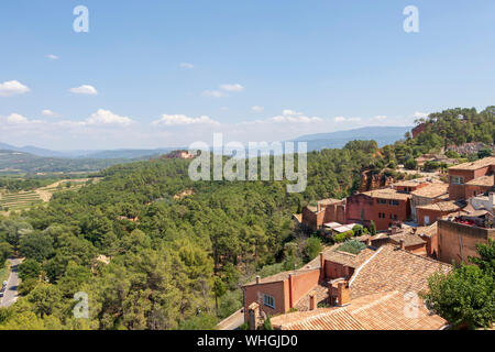 View on Roussillon village on the hilltop, small Provensal town with large ochre deposits, located within borders of Natural Regional Park of Luberon - Stock Photo