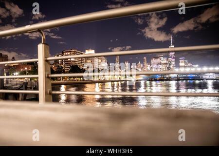 New York City view of skyline seen through railing on pier - Stock Photo