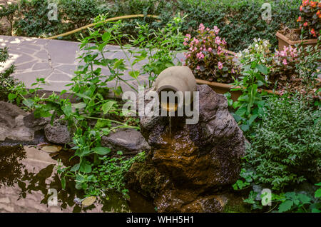 An artificial stream with running water from a clay pitcher lies on large stones surrounded by plants in the yard near a path covered with tiles - Stock Photo