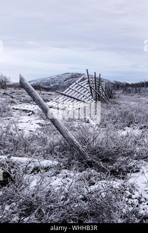 Damaged Fence On Snow Covered Field Against Sky - Stock Photo