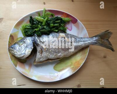 Directly Above Shot Of Baked Sea Bream With Vegetables In Plate On Table - Stock Photo