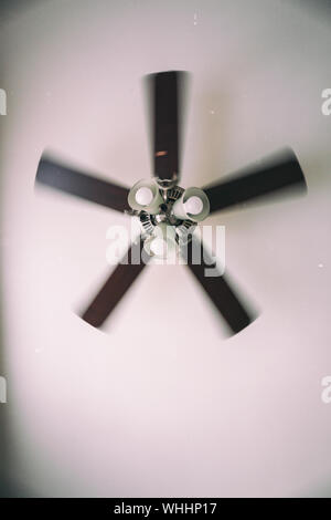 A vintage photo of an old electric ceiling fan installed into a ceiling lamp - Stock Photo